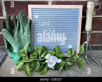 Love your garden. Gardening concept with felt letter board, handheld prune, dirty gloves and a pruned branch with blossom from an apple tree on a stone patio - Stock Photo