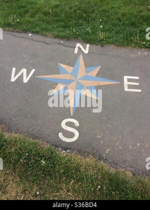 Compass points painted on footpath in play park in Stockton on Tees, England, UK - Stock Photo