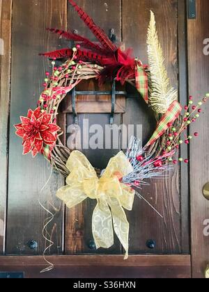 A wreath decorated in red and gold designs hangs on a wooden door. - Stock Photo