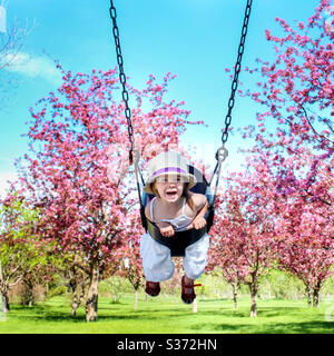 Little girl swinging on swing, cherry blossom trees in background - Stock Photo