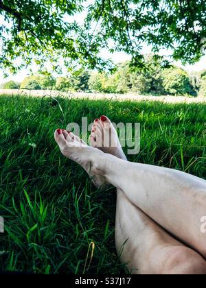 Woman's legs relaxing in a grass field