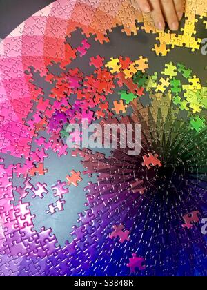Completing a large colorful jigsaw puzzle - Stock Photo
