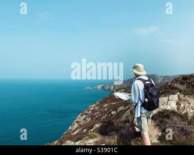 Walker, hiker, on coastal path between South Stack and North Stack at Gogarth Bay, Holyhead, Anglesey, North Wales - Stock Photo
