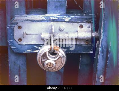 A round metal padlock and bolt on a blue wooden door - Stock Photo