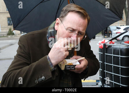 Erfurt, Germany. 16th Mar, 2019. Thuringia's Prime Minister Bodo Ramelow (The Left) bites into a Thuringian gourmet bag at the opening of the barbecue season 'RostKultur - Thüringen glows up'. 13 manufacturers of original Thuringian bratwursts present their sausages on the cathedral square. Credit: Bodo Schackow/dpa-Zentralbild/dpa/Alamy Live News - Stock Photo