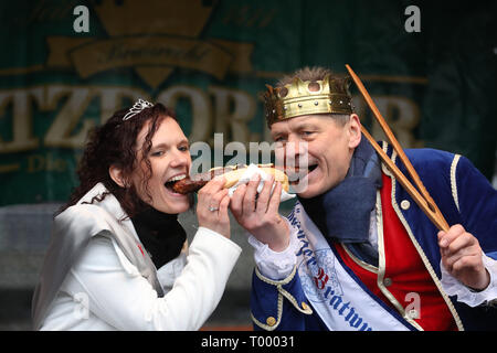 Erfurt, Germany. 16th Mar, 2019. Thuringia's sausage queen Jennifer Risch and Thuringia's bratwurst king Norbert Abt bite into a bratwurst at the opening of the barbecue season 'RostKultur - Thüringen glows up'. 13 manufacturers of original Thuringian bratwursts present their sausages on the cathedral square. Credit: Bodo Schackow/dpa-Zentralbild/dpa/Alamy Live News - Stock Photo