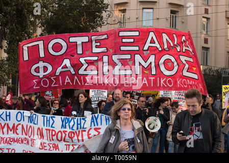 Athens, Greece. 16th March 2019. A banner reads, 'Never again fascism', as locals, migrants and refugees hold placards and shout slogans against racism and closed borders. Leftist and anti-racist organizations staged a rally on the occasion of the International Day against racism to demonstrate against discrimination and racist policies and behaviours. © Nikolas Georgiou / Alamy Live News - Stock Photo