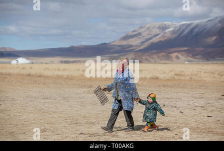 bayan Ulgii, Mongolia, 29th September 2015: mongolian kazakh nomad woman with her son in a landscape of Western Mongolia - Stock Photo