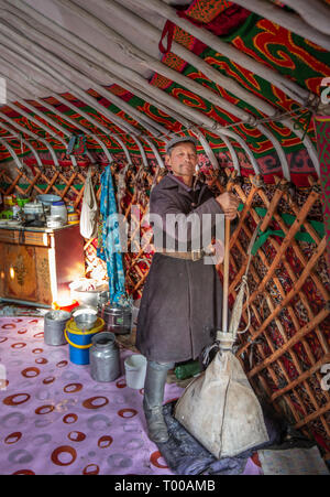 Bayan Olgii, Mongolia, 29th September 2015: Mongoilian kazakh nomad  man  helping out in making cheese - Stock Photo