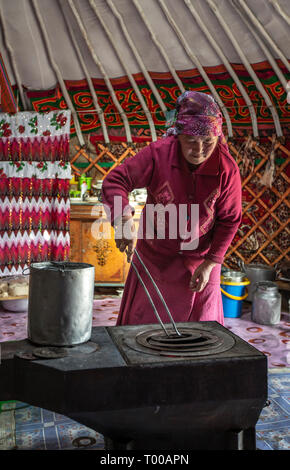 Bayan Olgii, Mongolia, 29th September 2015: Mongoilian kazakh nomad  woman cooking  in her home yurt - Stock Photo