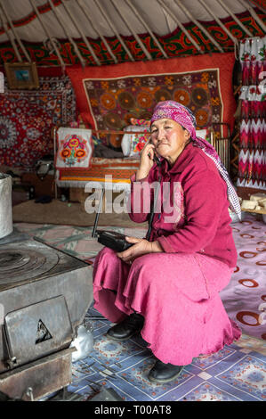 Bayan Olgii, Mongolia, 29th September 2015: Mongoilian kazakh nomad  woman on a phone  in her home yurt - Stock Photo