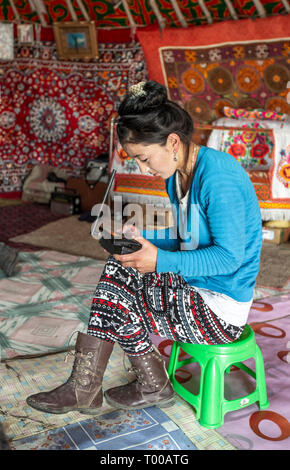 Bayan Olgii, Mongolia, 29th September 2015: Mongoilian kazakh nomad  woman waiting for a phone call  in her home yurt - Stock Photo