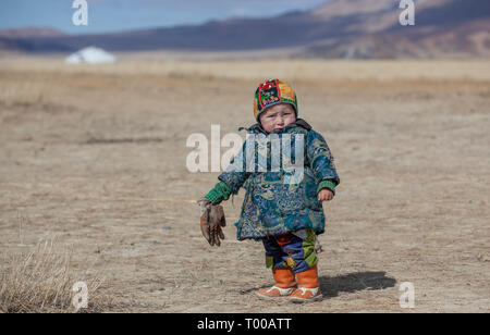 bayan Ulgii, Mongolia, 29th September 2015: mongolian kazakh nomad boy playing in a landscape of western mongolia - Stock Photo