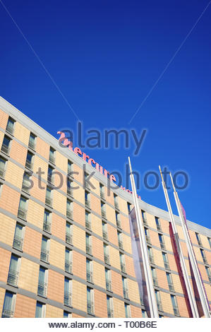 Poznan, Poland - October 31, 2018: Top of the Mercure Hotel building with flags in the foreground. - Stock Photo