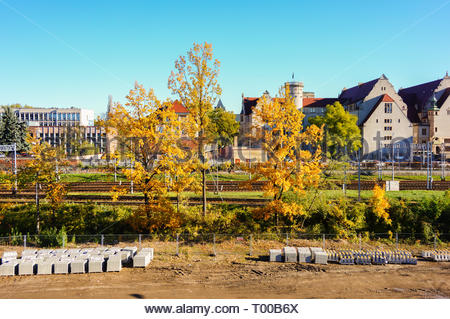 Poznan, Poland - October 31, 2018: Trees and construction area with university building in the background. - Stock Photo