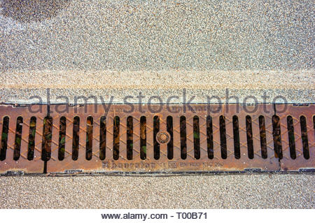 Poznan, Poland - October 31, 2018: Metal rain drain by a sidewalk in the city. - Stock Photo