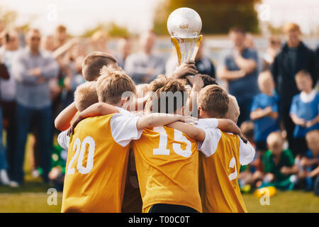 Kids Holding Golden Cup. Boys Winning Soccer Championship. Children Raising Trophy to the Sky in Sunny Summer Day. Football Champion Team - Stock Photo