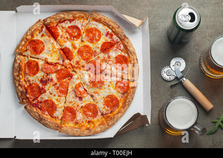 Italian fast food. Delicious hot pepperoni pizza in a box, and glass of beer sliced and served on brown table, close up view. Concept of fast food and - Stock Photo