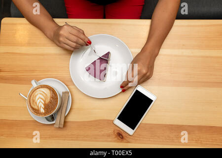 View from above on woman hands on wooden table hold coffe cup near cheesecake and smartphone. - Stock Photo