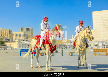Doha, Qatar - February 20, 2019: two heritage Police Officers in traditional 1940s Qatari uniform riding white Arabian Horses at square of Souq Waqif - Stock Photo