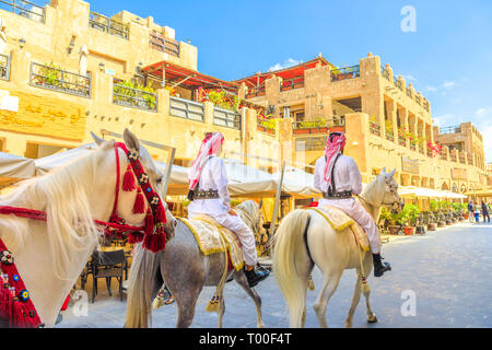 Doha, Qatar - February 20, 2019: heritage Police Officers in traditional 1940s Qatari uniform at old Souq Waqif riding white Arabian Horses on - Stock Photo