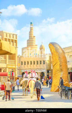 Doha, Qatar - February 20, 2019: two police officers riding white Arabian horses at Souq Waqif. Fanar Islamic Cultural Center with Spiral Mosque and - Stock Photo
