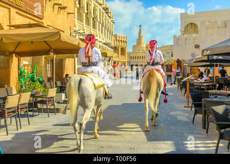 Doha, Qatar - February 20, 2019: Heritage Police Officers in traditional 1940s Qatari uniform at old Souq Waqif riding Arabian Horses. Fanar Islamic - Stock Photo