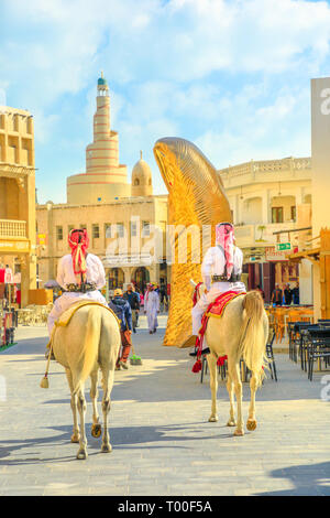 Doha, Qatar - February 20, 2019: two police officers riding white Arabian horses at Souq Waqif market. Fanar Islamic Cultural Center with Spiral - Stock Photo