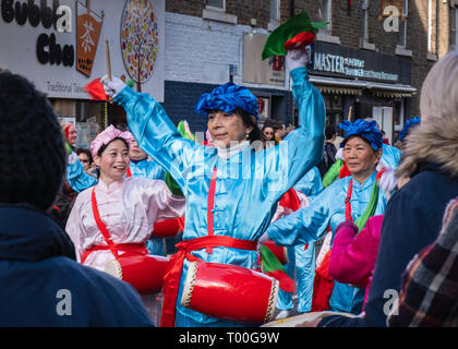Enthusiastic female drummer celebrating in parade during the Newcastle upon Tyne Chinese New Year celebrations - Stock Photo
