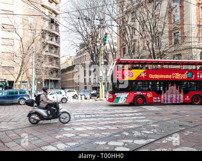 MILAN, ITALY - FEBRUARY 24, 2019: scooter, sightseeing bus, cars drive on street Foro Buonaparte in Milan city in spring day. Milan is capital of Lomb - Stock Photo
