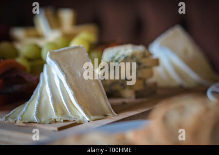 Cheese platter with different cheeses including brie, cheddar and blue cheese, served with grapes - Stock Photo