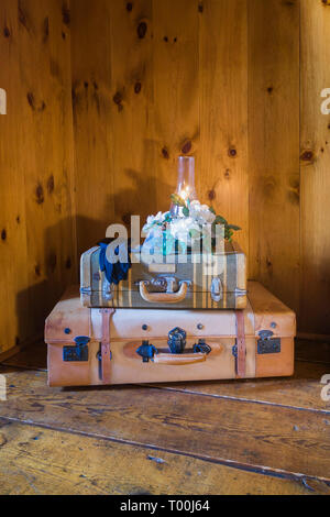 Lit candle on top of suitcases on hemlock wood plank flooring in upstairs master bedroom  inside an old circa 1760 Canadiana fieldstone home - Stock Photo