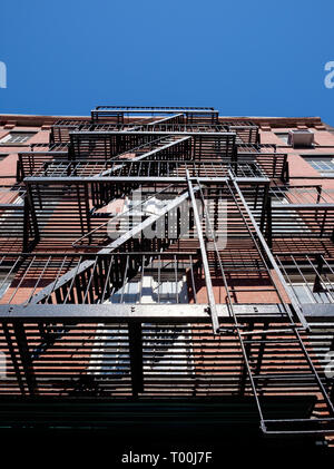 Iconic metal fire escapes on outside of building in Manhattan, New York City. March 2018 - Stock Photo