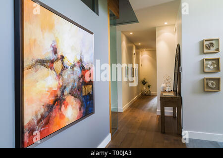Framed abstract painting on grey wall of hallway with hickory wood floorboards inside a luxurious contemporary bungalow style home - Stock Photo