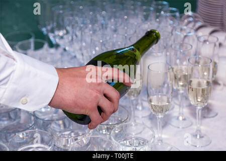 The waiter pours champagne into glasses from a bottle in a restaurant. Catering, banquet - Stock Photo