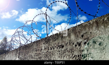 Barbed wire on a dark fence. Against a blue sky with clouds - Stock Photo