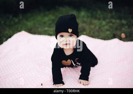 Little kid with cute eyes lying on pink blanket on ground. Stock Photo