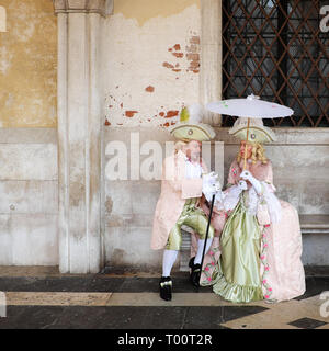 Couple dressed in traditional costume for Venice Carnival sitting at Doge's Palace, Piazza San Marco, Venice, Veneto, Italy - Stock Photo