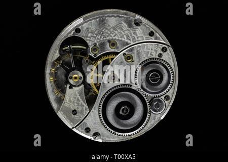 Very old, dusty and vintage hand watch mechanism isolated on black background - Stock Photo