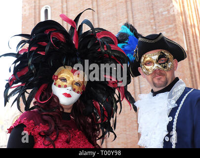 Couple dressed in traditional mask and costume for Venice Carnival standing in Piazza San Marco, Venice, Veneto, Italy - Stock Photo