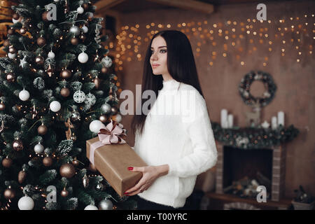 Beautiful woman with long dark hair in white sweater holds Christmas gift. - Stock Photo