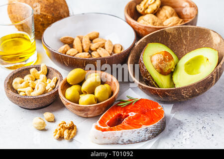 Selection of healthy fat sources: fish, nuts, oil, olives, avocado on white background. - Stock Photo