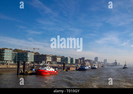 Tugboats anchoring at the river bank of the Elbe river in the harbour of Hamburg, Germany. - Stock Photo