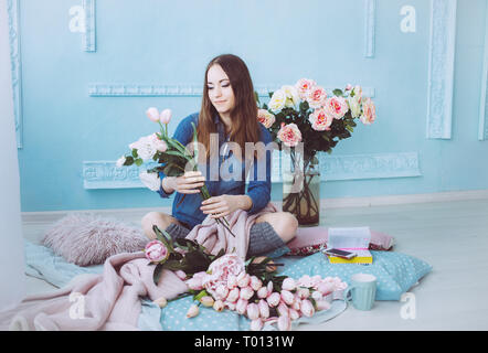 Cheerful young woman sitting on the floor, making flower bouquet of pink tulips in light sunlit room with blue walls. - Stock Photo