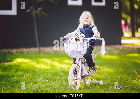Funny child Caucasian girl blonde near a purple bike with a basket and a zebra toy in an outside park on a green lawn grass cart at home. - Stock Photo