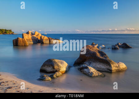 Granite rocks in the warm light of the setting sun at Anse Bateau. - Stock Photo