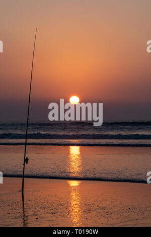 Silhouette of fishing rod at the edge of the Atlantic Ocean at sunset from Agadir beach, Morocco, Africa - Stock Photo