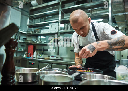 Delicate work. Famous confident chef with several tattoos on his arms garnishing pasta Carbonara in a restaurant kitchen. Food concept