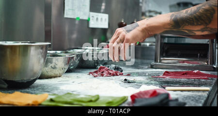 Cooking moments. Cropped image of chef's hands with beautiful tattoos making traditional italian pasta in restaurant kitchen. Close up - Stock Photo
