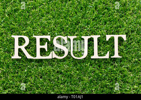 Wood alphabet in word result  on artificial green grass background - Stock Photo
